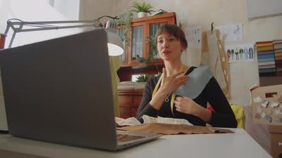 Female Dressmaker Discussing Fabric on Video Call