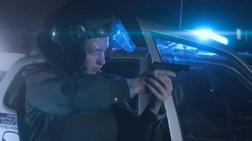 Ein Polizist zielt auf eine Waffe auf den Täter