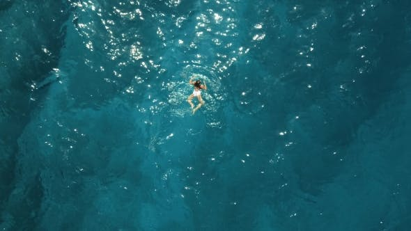 Thumbnail for Girl in a White Swimsuit Swimming in the Blue Sea