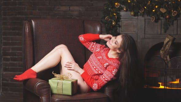 Thumbnail for Cute Redhead Girl in the Red Sweater Near Christmas Tree with Gifts in Hand