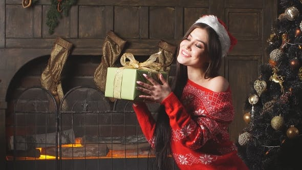 Thumbnail for Attractive Redheaded Girl Holding Christmas Gift and Smiling.