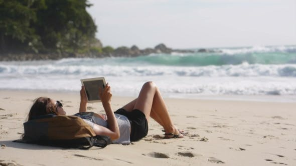 Thumbnail for Woman Traveler Freelancer Working with Tablet Computer on the Beach