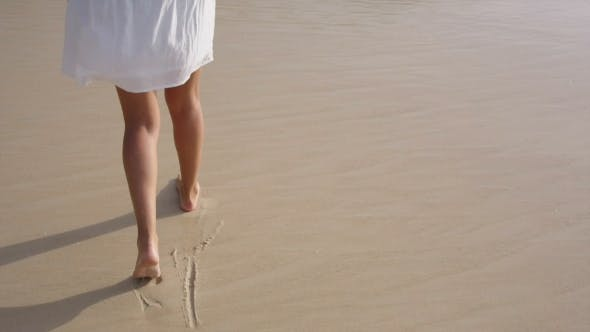 Thumbnail for Woman Legs Leave Footprints on the Sand, Wave Washes Away the Footprints
