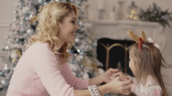Thumbnail for Young Mother Plays with Her Daughter Near the Christmas Tree