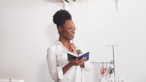 Portrait of Happy Black Woman Working As Fashion Designer and Dressmaker in Atelier.