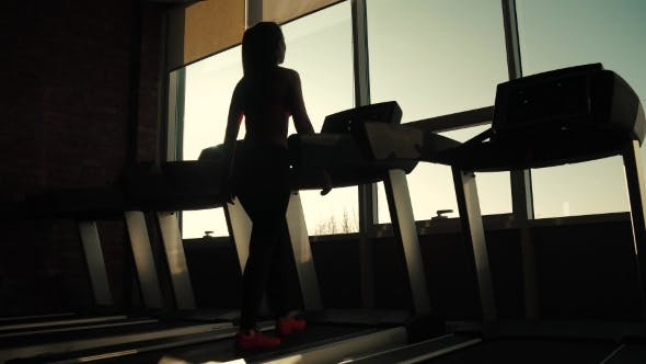 Thumbnail for Silhouette of a Girl on a Treadmill. Young Woman Walks on a Treadmill at the Gym. Cardio Exercises