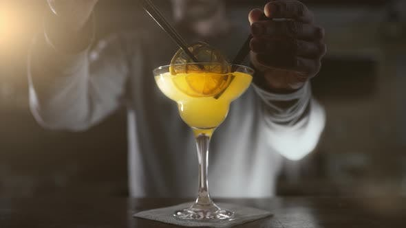 Thumbnail for Bartender Finishes the Cocktail in High Glass with Dried Fruits and Cocktail Straws, Making