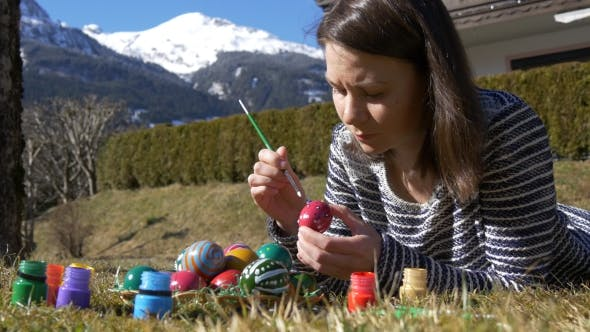 Thumbnail for Woman Lies on the Grass and Paints Easter Eggs