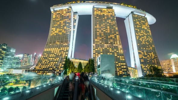 Cover Image for People Walk Along the Bridge To Marina Bay Sands at Night in Singapore. August 2017