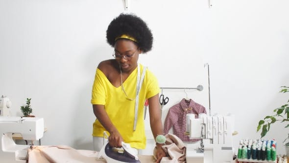 Thumbnail for Young Happy Dressmaker Ironing Pink Cloth in the Atelier.