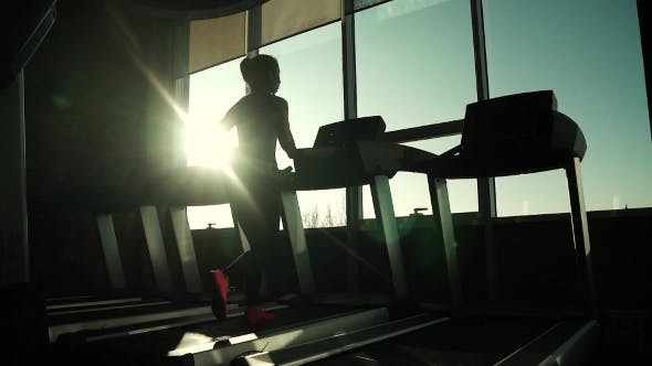 Cover Image for Cardio on the Treadmill. Exercises for Weight Loss. Silhouette of a Girl on a Treadmill