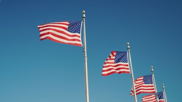Thumbnail for Several American Flags Are Fluttering in the Wind Against the Blue Sky. Near the Washington Monument