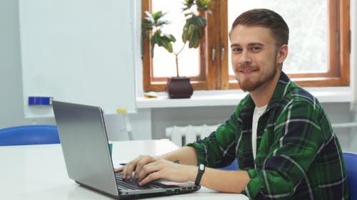 A Young Man Is Sitting at a Computer in an Educational Institution