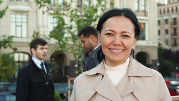 Thumbnail for The Woman Is Looking at Camera and Smiling at Background of Two Men Leading Business Negotiations