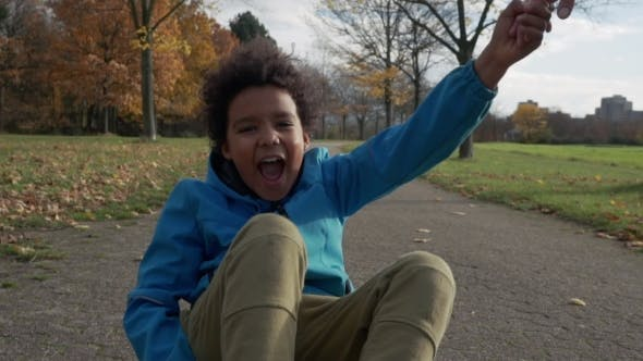 Cute Little Boy with Afro Hair Rides Sitting on Skateboard and Having Fun