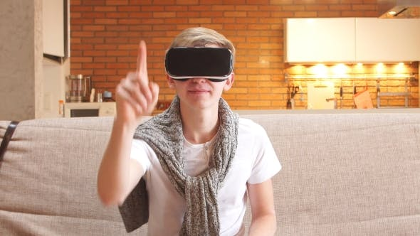 Thumbnail for Young Man Uses Virtual Reality Glasses in Home, in Living Room.