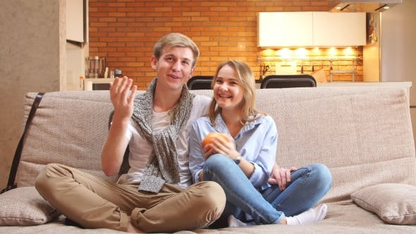 Thumbnail for Young Couple Watching TV on the Sofa in the Living Room. Hugging and Laughing Family Watching Comedy