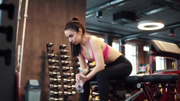 Thumbnail for Slender Sexy Girl Is Drinking Water From a Bottle in the Gym. Sportswoman in Sports Clothes Resting