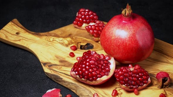 Cover Image for Pomegranate and Seeds  on Dark Concrete Background