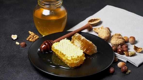 Cover Image for Honeycomb with Honey on Plate on Dark Concrete Background