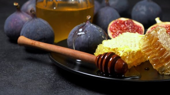 Figs with Honey on in the Plate on Dark Concrete Background