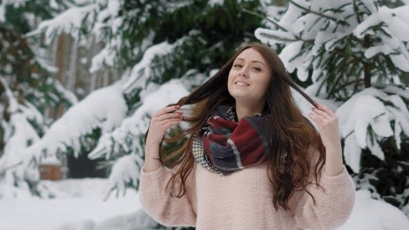 Thumbnail for Smiling Cute Brunette Girl Is Standing Outdoors Near Huge Snowy Spruces in Winter Day