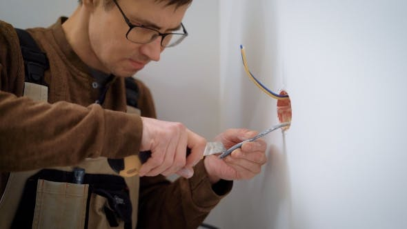 Thumbnail for Wireman Is Stripping Wires for Installation Sockets, Cutting a Cable Sheath, Using Stationery Knife