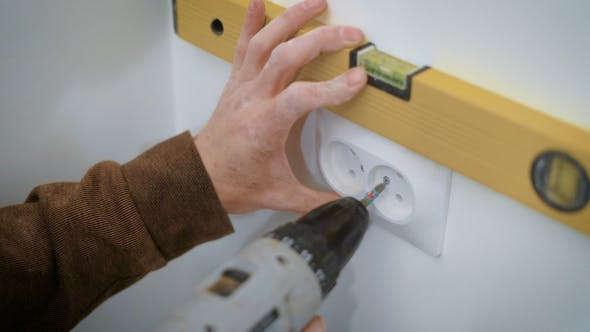 Thumbnail for Wireman Is Mounting a Double Socket on a White Wall Inside a Flat, Aligning and Twisting Bolts