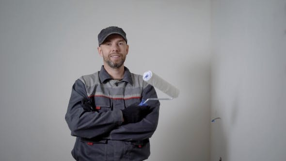 Thumbnail for Cheerful Repairman Is Standing in Apartment, Holding Paint Roller, Crossing Hands