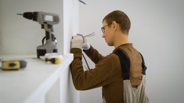Thumbnail for Electrician Is Cutting Wires and Trying on a Mechanism Recessed Socket in a White Wall