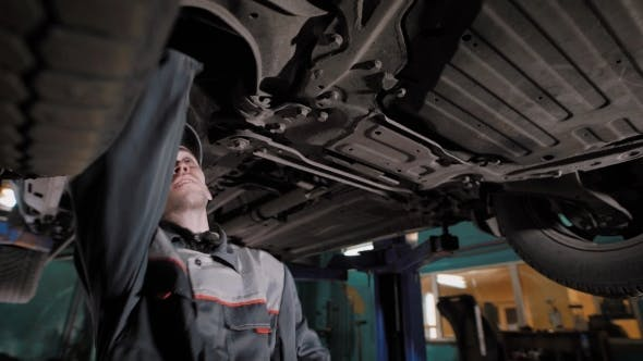 Thumbnail for Car Mechanic Standing Under Car