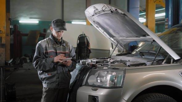 Thumbnail for Car Mechanic with Tablet Near Car