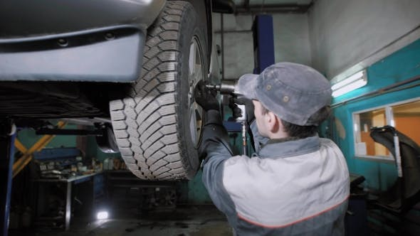 Thumbnail for Car Mechanic Removing Wheel From Car