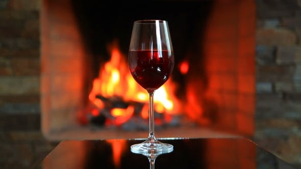 Thumbnail for Wineglass with Red Wine Near a Fireplace