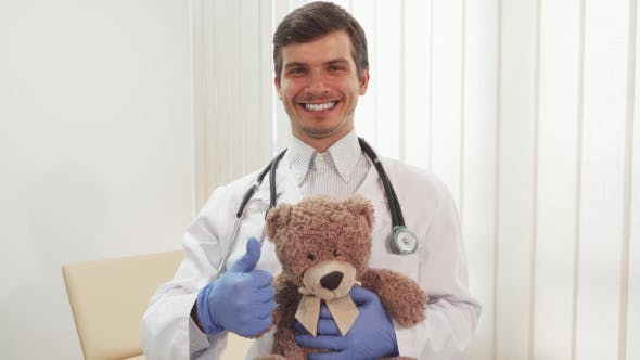 Thumbnail for Happy Doctor Showing Thumb Up Holding a Teddy Bear