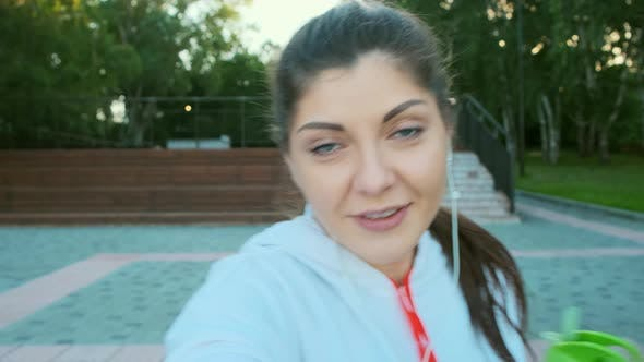 Thumbnail for Attractive Young Woman Blogger in a Sports Sweatshirt Is Recording Video for Vlog Before Jogging.