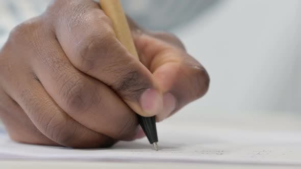 Close Up of African Man Writing on Paper with Pen