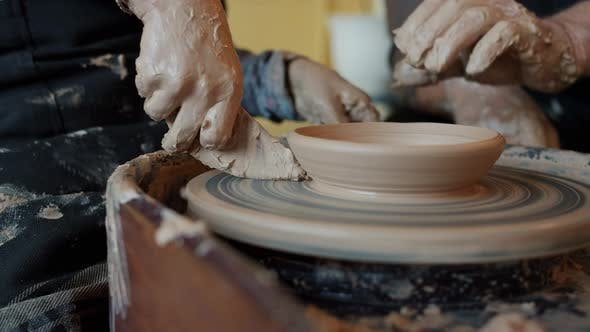 Close-up of People Man and Boy Making Bowl From Clay Using Tools in Workshop