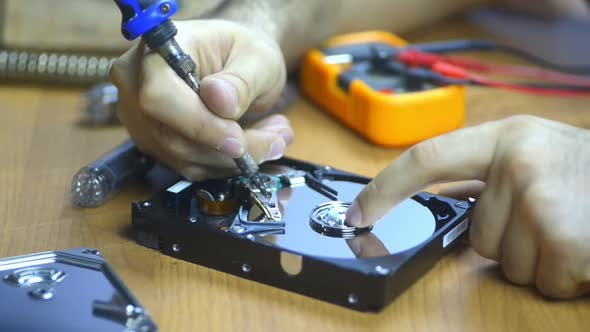 Computer Technician Repairing Hard Drive at Desk with Tools and Electronic Components Technology