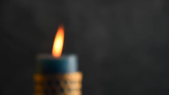 Blue candle trembling flame with grey background focusing in and blown out
