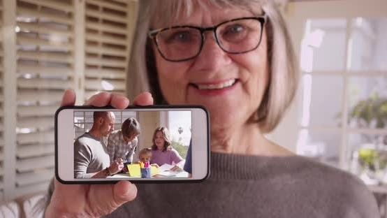 Thumbnail for Grandmother showing off footage of her spending time with family on smartphone