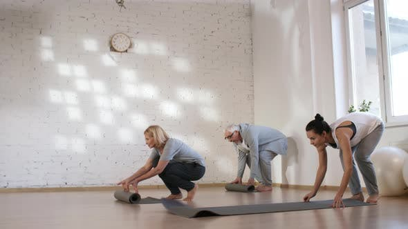 Cover Image for Caucasian Yoga Teacher and Client Couple Rolling out Mats