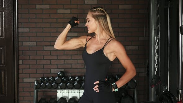 Thumbnail for Woman Bodybuilder Showing the Biceps in the Gym