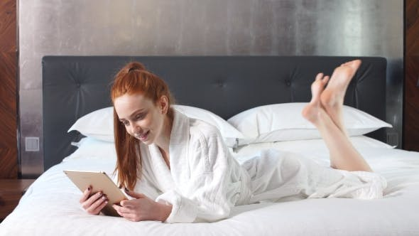 Thumbnail for Young Redhead Woman Using Tablet Computer Lying on Bed in Hotel Room.