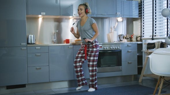 Cover Image for Woman Singing and Dancing in Kitchen