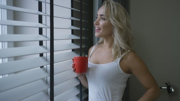 Cover Image for Cheerful Woman with Mug Looking Out Window