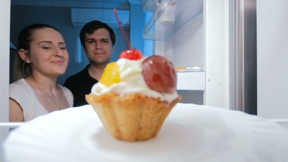 Thumbnail for Young Couple Looking for Something To Eat in Fridge and Taking Sweet Cake