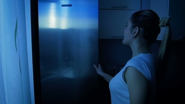 Woman Taking Fresh Apple From Refrigerator at Night. Concept of Healthy
