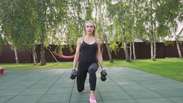 Thumbnail for Fitness Woman Doing Walking Lunges with Dumbbells on Sportsground