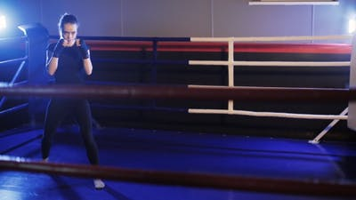Young Woman Punches in Boxing Gym. Shadow Boxing
